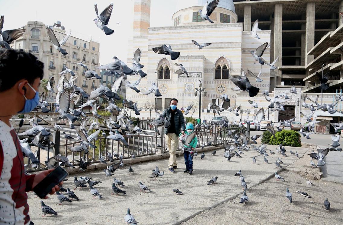 people_wearing_face_masks_walk_in_damascus_syria._epa.jpg